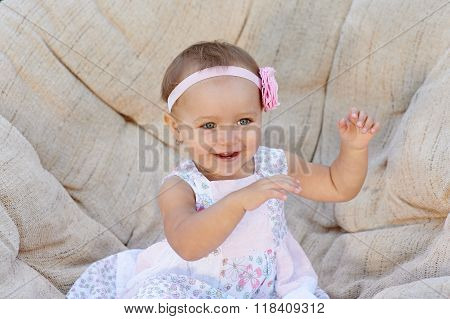 Little Baby Girl Poses On A White Chair.  She Is Smiling Happily