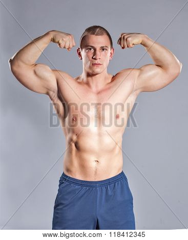 Young Muscular Man Showing His Biceps On Gray Background