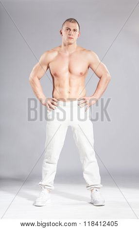Young Sporty Muscular Man Ready To Workout On Gray Background