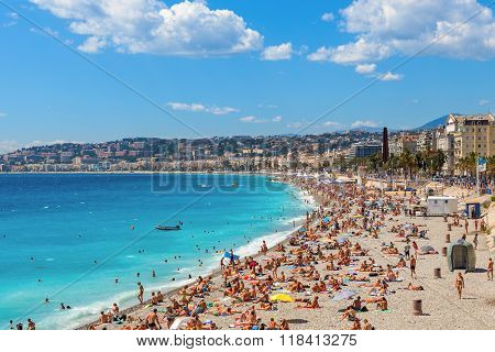 NICE, FRANCE - AUGUST 23, 2014: Public beach along seashore and Promenade des Anglais in Nice - famous and popular resort, fifth most populous and second-largest French city on Mediterranean coast.