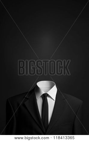 Surrealism And Business Theme: A Man Without A Head In A Black Suit On A Dark Background In The Stud