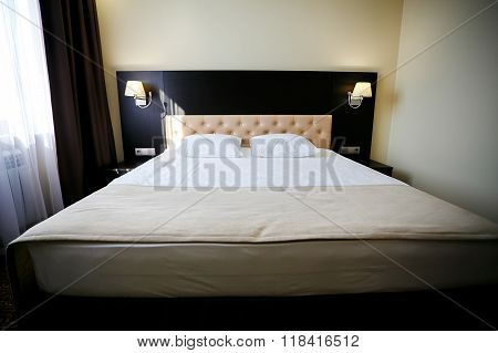 Double bed in ordinary hotel room. Daylight as background. Housekeeping, room service, cleaning.