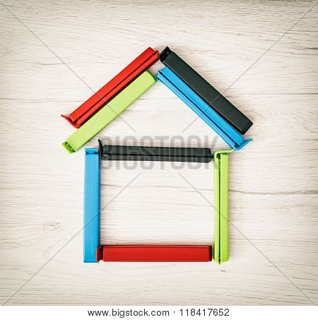 House Shape Of Colorful Bag Clips On The Wooden Background