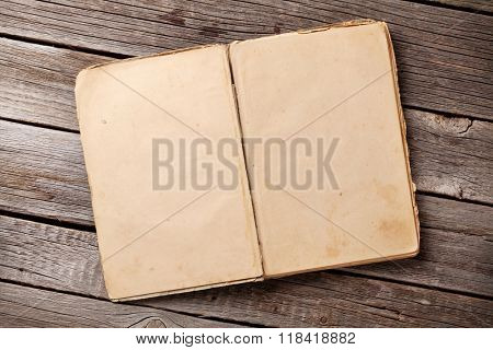 Open vintage book on wooden background. Top view with copy space