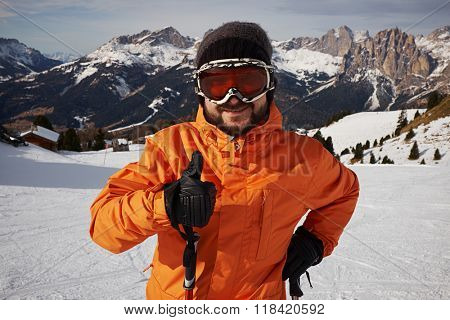 smiley skier showing thumbs up and looking at camera against mountainside