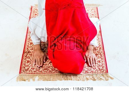 Asian Muslim woman praying with Quran and beads chain wearing traditional dress