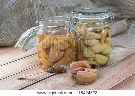 Two Preserved Pear In Glass Jar On Wooden Table With Pear Compote