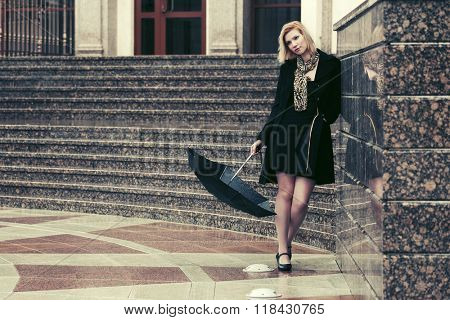 Sad young fashion woman in black coat with umbrella at the wall