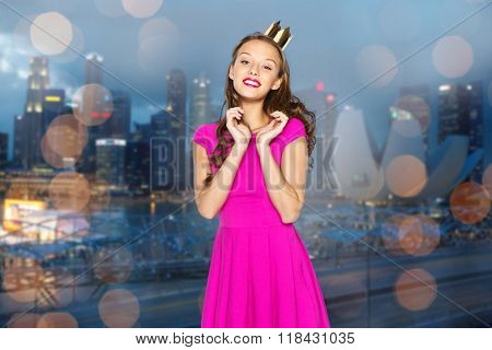 people, holidays, night life and fashion concept - happy young woman or teen girl in pink dress and princess crown