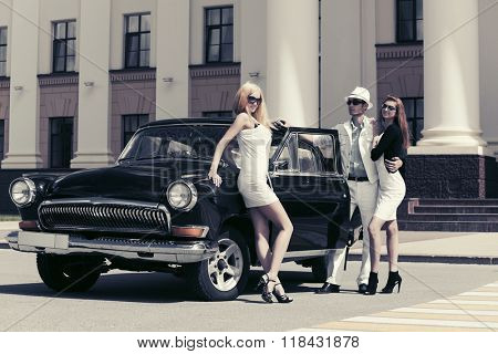 Happy young fashion man and women standing by retro car