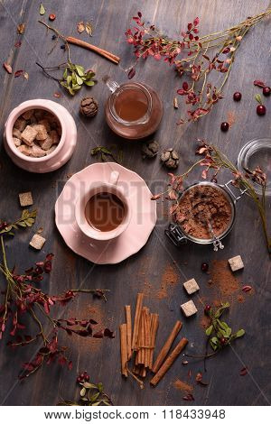 Cocoa drink with cinnamon, fresh cocoa powder, cane sugar on rustic wooden background, top view.
