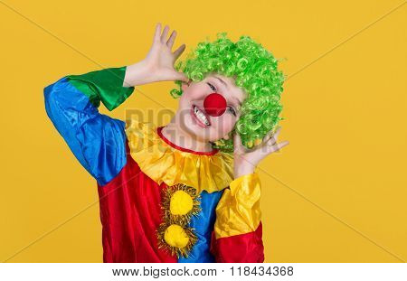 Funny Clown Isolated On Yellow Background. Closeup Of Little Clown In Green Wig.