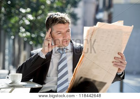 Attractive Businessman Sitting Outdoors Having Coffee  Reading Newspaper News Relaxed