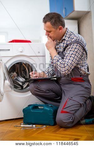 Repairman is repairing a washing machine on the white background. Entering malfunction