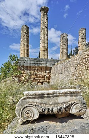 Ancient column and The Temple of Apollo in Ancient Greek archaeological site of Delphi, Greec
