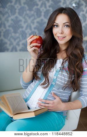 Beautiful pregnant woman with a book in his hands