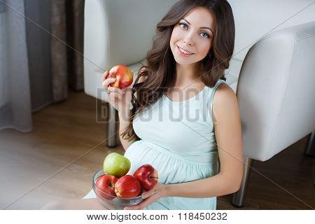 Beautiful young pregnant woman with apples.