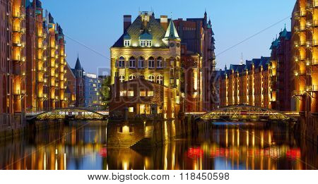 Panorama of Old Speicherstadt in Hamburg illuminated at night. Sunset background