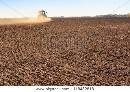 Cultivator Operates On Ploughed Field Near Spring Forest