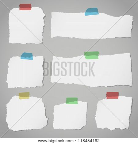 Pieces of torn white blank note paper with colorful sticky tape on gray background