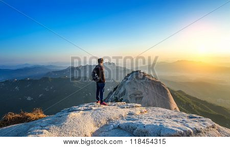 Man Stands On The Peak Of Stone In Bukhansan National Park,seoul In South Korea And Watching To Sunr