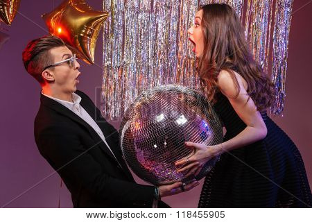 Attractive amazed young couple holding disco ball over purple background