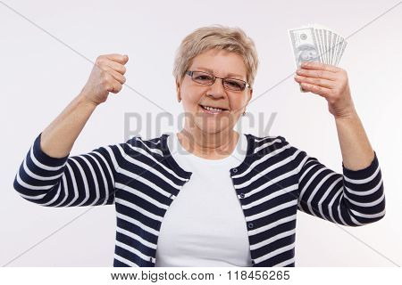 Happy Senior Female Holding Currencies Dollar And Clenching Her Fist, Concept Of Financial Security