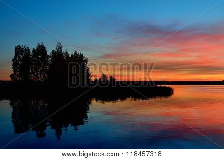 Small island with trees reflecting in still lake water during beautiful orange sunrise.
