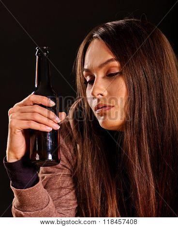 Portrait of drunking girl keeps bottle of alcohol. Soccial issue alcoholism.