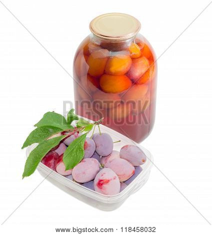Fresh Plums In Tray And Canned Plums In Glass Jar