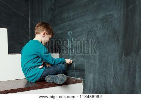 Little Boy Is Drawing On A Blackdoard