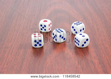 Five Traditional Six-sided Dice On Wooden Surface