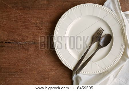 Empty Dish With Wooden Spoon And Fork On Old Wooden Background