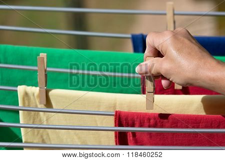 Hands putting T-shirts clothesline to dry
