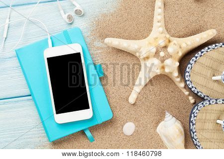 Smartphone and notepad on wooden table with starfish and shells. Top view with copy space
