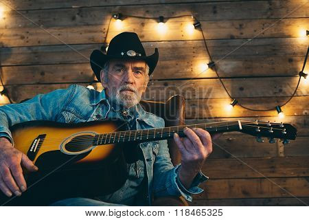 Guitar Playing Senior Country And Western Musician With Beard Sitting In Chair.