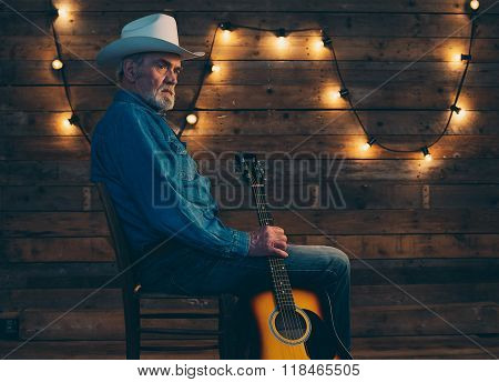 Senior Bearded Country And Western Musician Sitting On Chair Holding Guitar In Front Of Wooden Wall