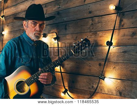 Senior Bearded Country And Western Musician Holding Guitar Standing In Front Of Wooden Wall With Lig
