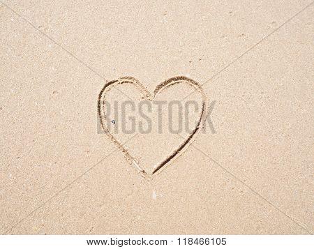 Heart-shape drawing on the sandy beach