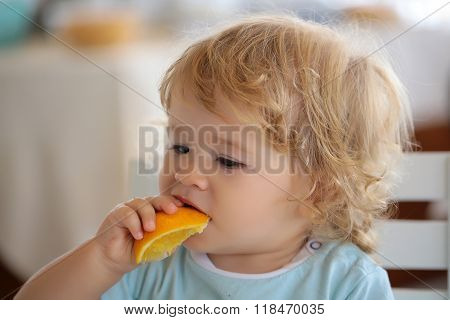 Portrait Of Kid Eating Orange