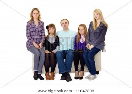 An Ordinary Large Family Sitting On Couch