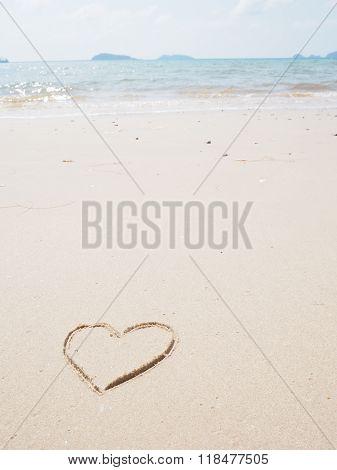 Heart-shape drawing left-side on the sandy beach
