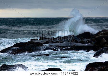 Large Ocean Wave Crashing on Dark Rocks