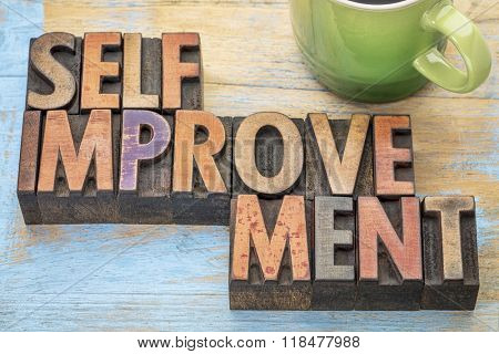 self improvement  - word abstract in letterpress wood type printing blocks stained by color inks with a cup of coffee
