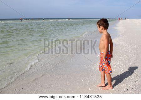 Young boy standing on a sandy beach beside the ocean