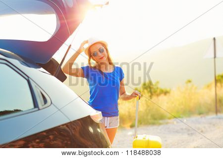 Woman With A Yellow Suitcase Standing Near The Trunk Of A Car Parked On The Roadside