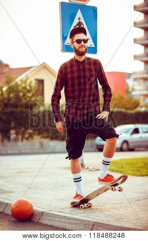 Young Man In Sunglasses With A Skateboard On A Street In The City At Sunset Light