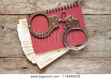 Handcuffs On Notebook With Euro Banknotes