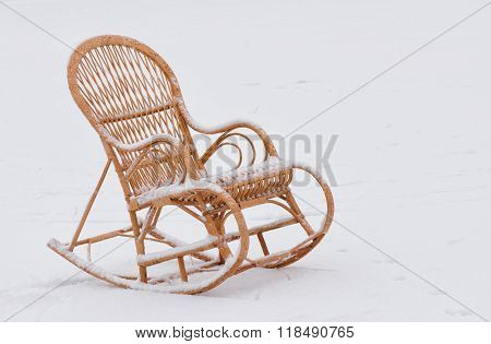 Wicker rocking-chair on the fresh snow waiting for master
