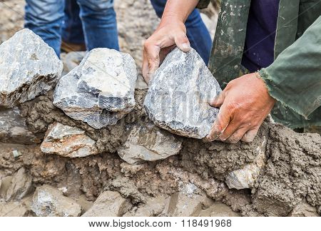 Hands Working On Masonry Stone Wall